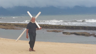 man walking with cross
